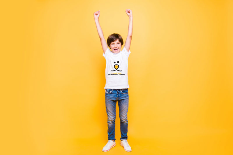 Full height portrait of attractive young cheerful school boy, smiling standing raising hands up over yellow background, isolated. Copy space